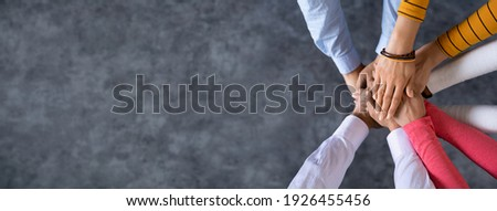 Close up top view of young business people putting their hands together. Stack of hands. Unity and teamwork concept. Royalty-Free Stock Photo #1926455456