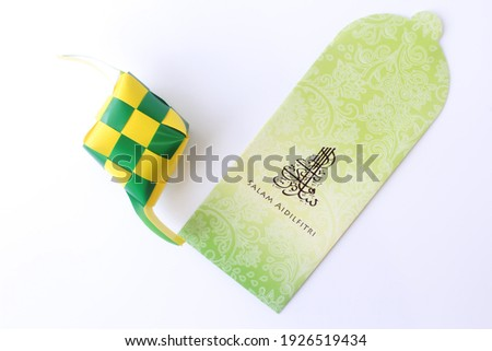 """Top view money packet with malay words that mean """"Happy Hari Raya"""" with arabic fonts and Rice Dumpling (Ketupat) besides money packet isolated on white background. Happy eid Mubarak. Royalty-Free Stock Photo #1926519434"""