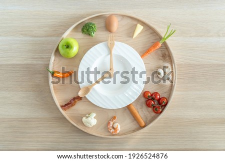 Intermittent fasting IF and ketogenic diet concept with 8-hour clock timer for eating nutritional or keto LCHF low carb high fat food meal healthy dish and 16-hour skipping meal for weight loss Royalty-Free Stock Photo #1926524876