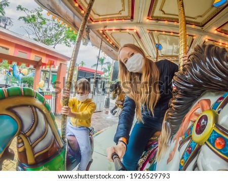 Family wearing a medical mask during COVID-19 coronavirus at an amusement park Royalty-Free Stock Photo #1926529793