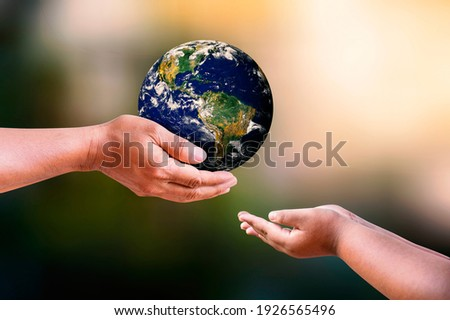 Father and daughter holding earth in hands on blur nature backgrounds. Earth day concept. Elements of this image furnished by NASA. Royalty-Free Stock Photo #1926565496