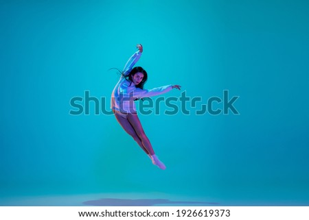 Flying. Young and graceful ballet dancer isolated on blue studio background in neon light. Art, motion, action, flexibility, inspiration concept. Flexible caucasian ballet dancer, moves in glow. Royalty-Free Stock Photo #1926619373