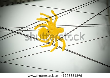 Yellow plastic spider. Cobweb made of stretched threads. Abstract white background with vignetting.