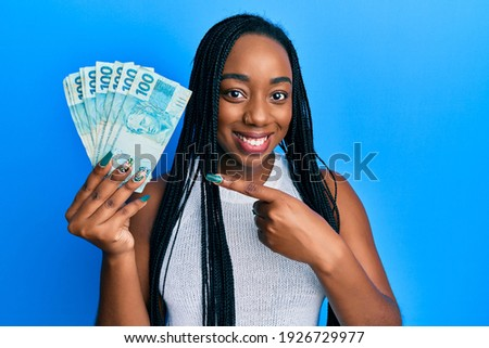 Young african american woman holding 100 brazilian real banknotes smiling happy pointing with hand and finger  Royalty-Free Stock Photo #1926729977