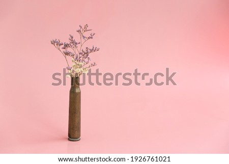 Dried flowers in an empty case from under a firearm on a pink background Royalty-Free Stock Photo #1926761021