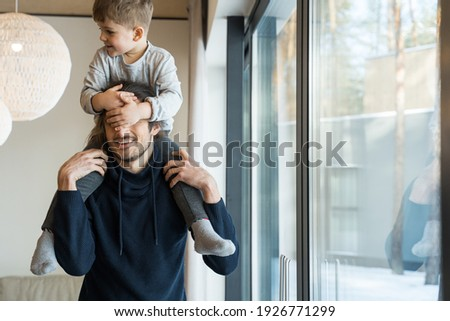 My best friend. Happy bearded father holding his son at the shoulders near the window while spending free time together at home. Stock photo