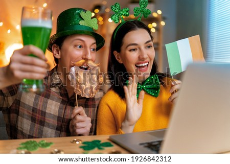 Happy family couple celebrating St. Patrick's Day with their friends by online at home. Royalty-Free Stock Photo #1926842312
