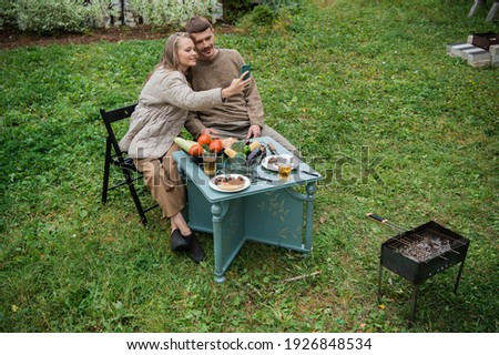 Fun time in self-isolation. A guy and a girl had a delicious picnic with grilled vegetables and meat. Make a joint photo on your smartphone for memory