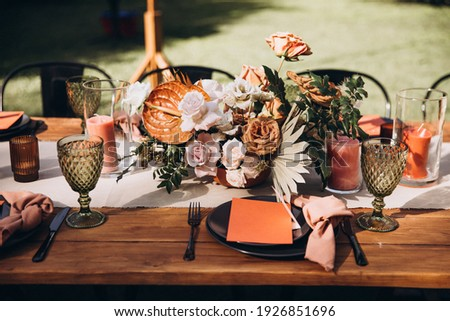 Wedding decor. Banquet. Glasses and plates, cutlery, candles and flower arrangements are on a wooden table in the garden Royalty-Free Stock Photo #1926851696
