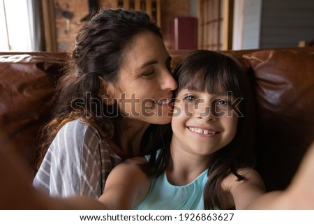 Cute small 8s Hispanic girl child have fun with young mother make self-portrait picture on camera together. Little Latino kid take selfie on cellphone with mom, enjoy family weekend at home.