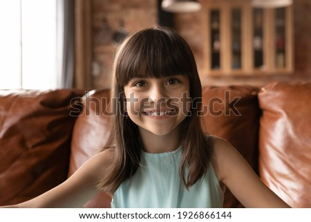 Close up headshot portrait of happy small 8s Latino girl child have webcam online talk on gadget at home. Smiling little Hispanic kid look at camera speak on video call. Virtual event concept.