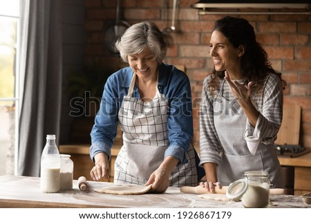 Overjoyed adult Hispanic girl with senior mom make dough bake cookies pastries together on weekend. Happy millennial Latino woman with mature mother have fun cooking dessert at home kitchen.