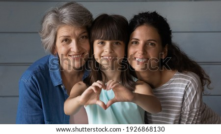 Close up family portrait of happy three generations of Hispanic women pose together show love heart hand gesture. Smiling little Latino girl child with young mother and senior grandmother feel united. Royalty-Free Stock Photo #1926868130