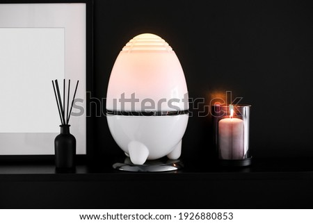 night light, ultrasonic humidifier and candle on a black background. cozy home corner. picture frame and photo mockup