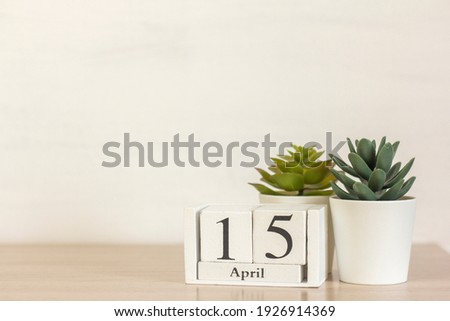 A wooden calendar with the date April 15 on the desktop. Royalty-Free Stock Photo #1926914369