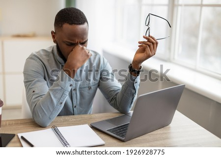 Eyes Fatigue. Tired African Businessman Holding Eyeglasses Massaging Nosebridge After Work On Computer Sitting In Modern Office. Glaucoma And Poor Eyesight Problem. Selective Focus Royalty-Free Stock Photo #1926928775