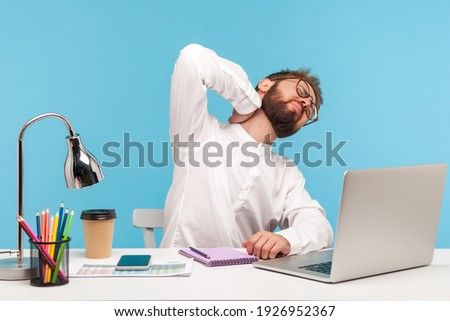 Overworked man office worker rubbing numb neck and shoulders, vertebral column problems, consequences of sedentary lifestyle, spine injury. Indoor studio shot isolated on blue background Royalty-Free Stock Photo #1926952367