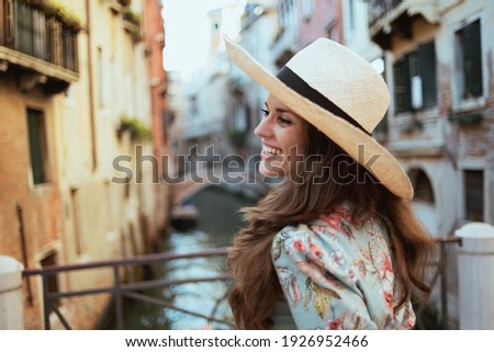 happy stylish tourist woman in floral dress with hat sightseeing in Venice, Italy. Royalty-Free Stock Photo #1926952466