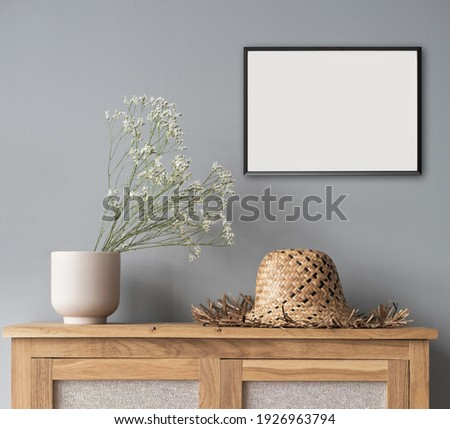 Small picture frame mockup on gray wall. Artwork in modern interior design. Empty white copy space for artwork showcase. Royalty-Free Stock Photo #1926963794