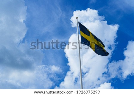 An isolated Swedish flag against the blue sky on a flagpole. Blue and yellow symbol of patriotism in Sweden.  Royalty-Free Stock Photo #1926975299