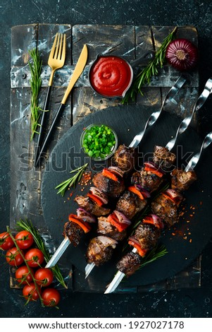 Traditional Kebab. Juicy pork skewers with vegetables on a black stone plate. Barbecue. Top view. Free space for text. Royalty-Free Stock Photo #1927027178