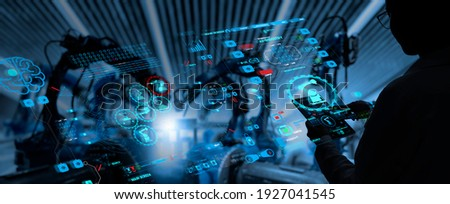 Factory Female Industrial Engineer working with automation robot arms machine in intelligent factory industrial on real time monitoring system software.Digital future manufacture. Royalty-Free Stock Photo #1927041545
