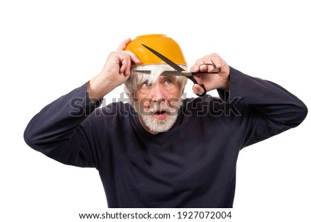 Horizontal shot of an old man giving himself a haircut using a yellow bowl on his head during the pandemic.  White background. Royalty-Free Stock Photo #1927072004