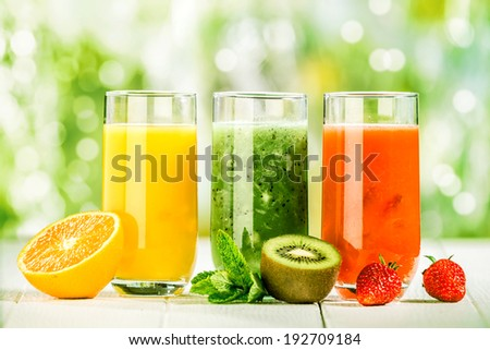 Trio of fresh healthy fruit juice blends in tall glasses on a summer picnic table outdoors with orange, kiwifruit with mint and strawberries #192709184