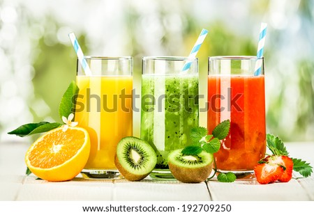 Delicious array of fresh fruit juices served in tall glasses made from liquidised orange, kiwifruit with peppermint, and strawberries for healthy summer treats rich in vitamins #192709250