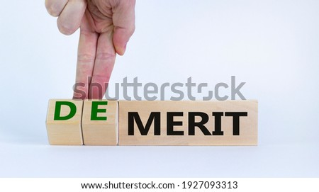 Demerit or merit symbol. Businessman turns wooden cubes and changes words 'demerit' to 'merit'. Beautiful white background, copy space. Business and demerit or merit concept.