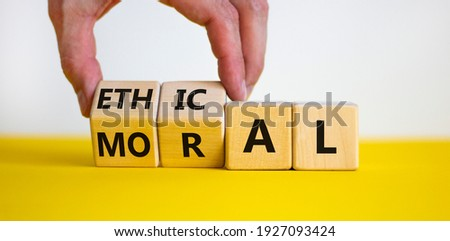 Ethical or moral symbol. Businessman turns wooden cubes and changes the word 'moral' to 'ethical' on a beautiful yellow table, white background. Business and ethical or moral concept. Copy space.
