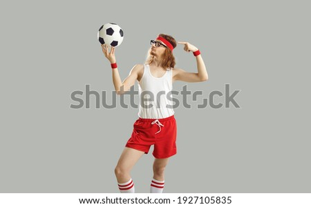 Funny crazy nerdy man in glasses and headband holding soccer ball. Proud young male football player in white tank top and red shorts standing isolated on grey background. Humorous sport concept