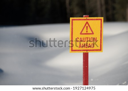 red and yellow warning caution ahead sign before frozen pond thin ice in winter with sunny warmer weather fresh white snow horizontal format room for type