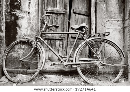 Black and white  old bicycle  in front of door / Old bicycle