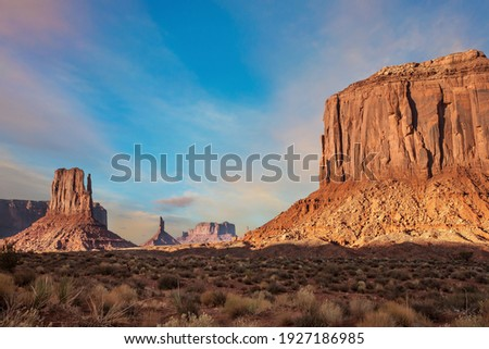 The famous cliffs Mittens in Monument Valley. The rocks - outcrops made of red sandstone. Bright multi-color sunset on the red stone valley. The concept of active, environmental and photo tourism Royalty-Free Stock Photo #1927186985