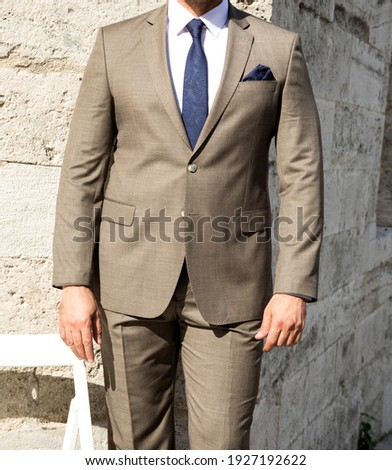green tone male suit on a mannequin combined different poses old Gothic style photographed in front of the stone wall fashion trend Textile male lifestyle business man buying.