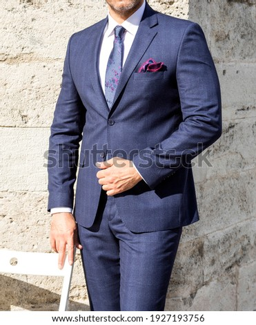 blue male suit combined on live mannequin in front of old gothic style stone wall photographing luxury male lifestyle what new fashion textile trend men's clothing business man buying.