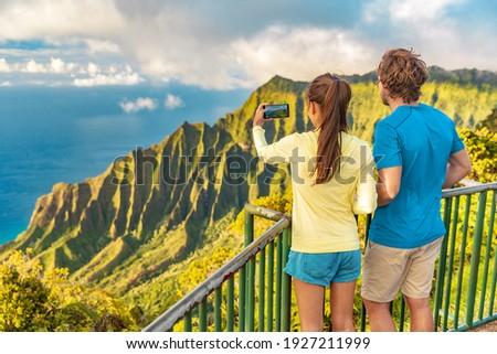 Hawaii Kauai island travel tourists couple taking phone picture of Na Pali Coast mountain range at sunset. USA famous vacation destination.