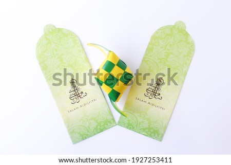 """Top view money packet with malay words that mean """"Happy Hari Raya"""" with arabic fonts and Rice Dumpling (Ketupat) besides money packet isolated on white background. Happy eid Mubarak Royalty-Free Stock Photo #1927253411"""