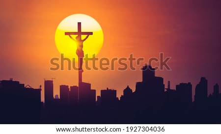Picture of Jesus cross with silhouette of skyscrapers in the city at sunrise