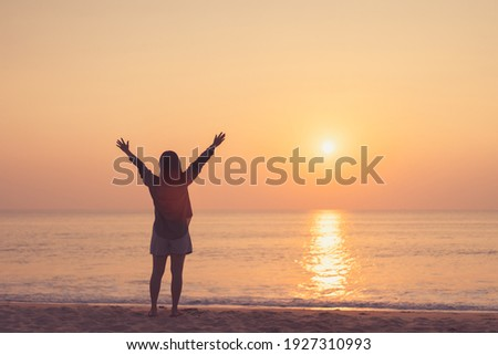 Copy space of woman rise hand up on sunset sky at beach and island background. Freedom and travel adventure concept. Vintage tone filter effect color style. Royalty-Free Stock Photo #1927310993