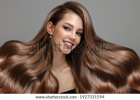 Portrait of a beautiful brunette woman with long wavy hair. Copycpase Royalty-Free Stock Photo #1927331594