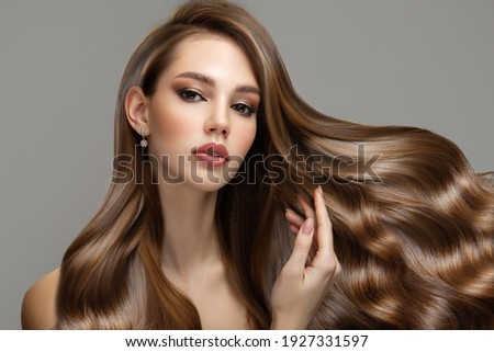 Portrait of a beautiful brunette woman with long wavy hair. Copycpase Royalty-Free Stock Photo #1927331597