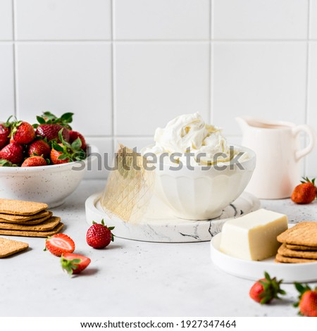 No Bake Strawberry Cheesecake Ingredients: Butter and Crackers for the Crust, Cream Cheese, Cream, Gelatin and Strawberries for the Filling, square Royalty-Free Stock Photo #1927347464