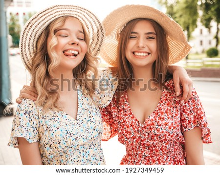 Two young beautiful smiling hipster female in trendy summer sundress.Sexy carefree women posing on the street background in hats. Positive models having fun and hugging