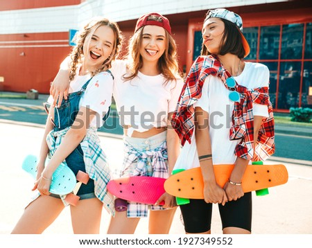 Three young smiling beautiful female with colorful penny skateboards. Women in summer hipster clothes posing in the street background. Positive models having fun and going crazy