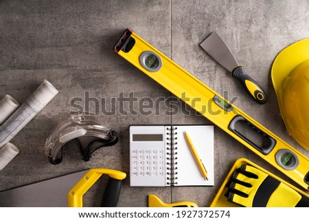 Yellow and black contractor equipment on gray tiles. Royalty-Free Stock Photo #1927372574