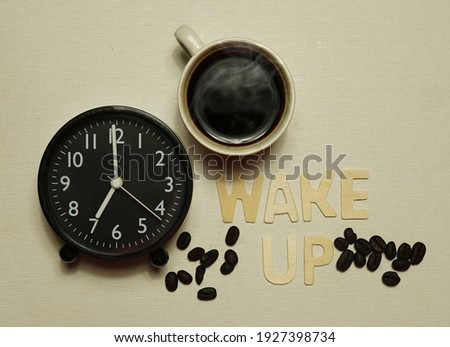 Abstract analog clock, coffee cup and coffee bean and wooden lettering picture. Awakening concept, top view Text copy space Focus on the coffee cup.