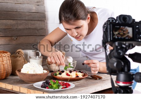 Professional food blogger taking pictures of pastry on table with dslr camera. Female photographer taking pictures of sweet food, camera mounted on tripod