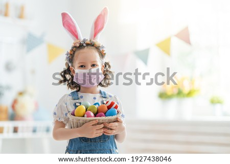 Beautiful child with painting eggs. Happy family preparing for Easter. Cute little girl is wearing bunny ears and face mask. Royalty-Free Stock Photo #1927438046